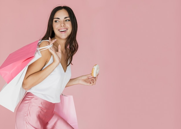 Woman with shopping bags and a donut on pink background Free Photo