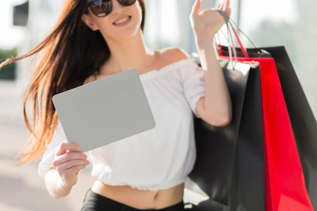 Woman with shopping bags and empty banner Free Photo