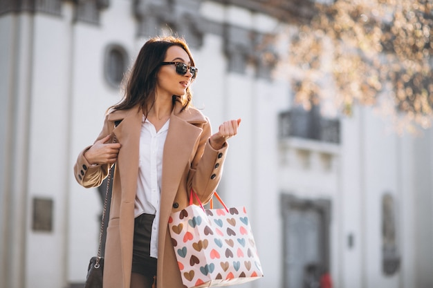 Woman with shopping bags outside the street Free Photo