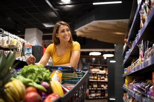 スーパーマーケットで食べ物を買うショッピングカートを持つ女性 無料写真