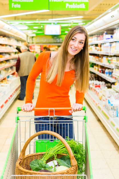 Woman with shopping cart in supermarket Premium Photo