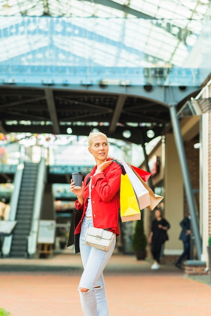 Woman with shopping packets in mall Free Photo