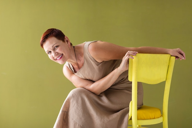 Woman with short hair sitting on chair Free Photo