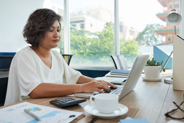 Woman with short wavy hair sitting at desk in office and working on laptop Free Photo