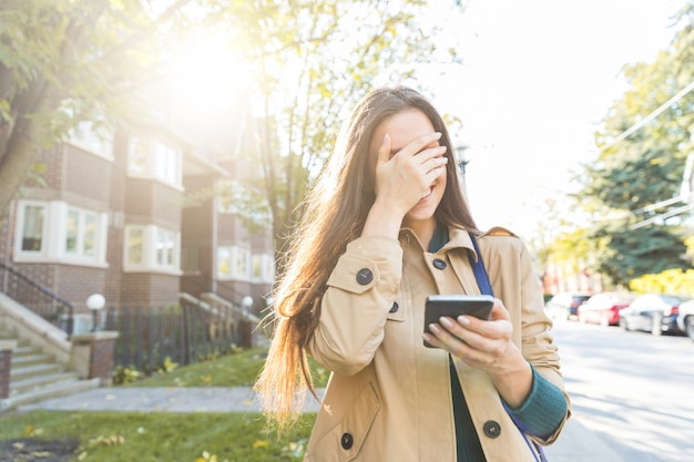 Woman with smartphone laughing and covering face with hand Premium Photo