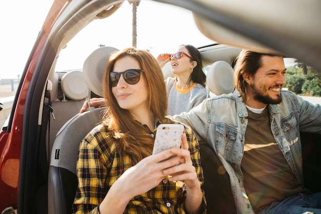 Woman with smartphone and positive man in car near lady leaning out from auto Free Photo
