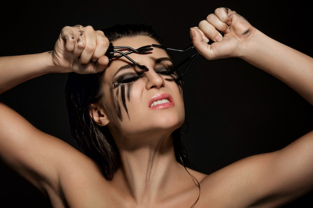Woman with smudges of makeup on her face and broken mascara brushes Premium Photo