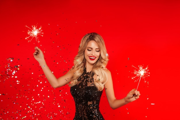 Woman with sparkler celebrating new year party. portrait of beautiful smiling girl in shiny black dress throwing confetti Premium Photo