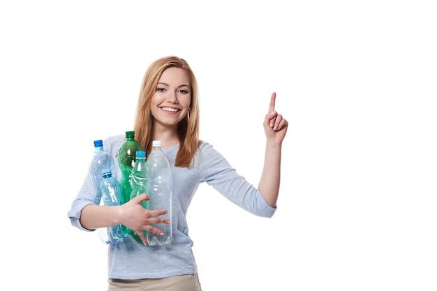 복사 공간에서 가리키는 플라스틱 병의 스택을 가진 여자 무료 사진