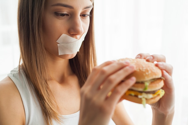 Woman with a stuck mouth tries to eat bad food Premium Photo