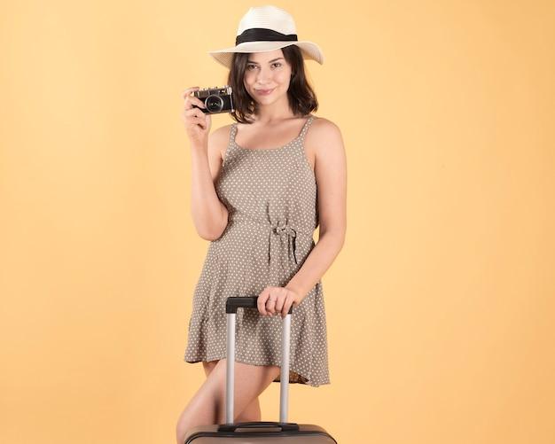 スーツケースの帽子と写真カメラの旅行者、観光客を持つ女性。黄色の背景に Premium写真