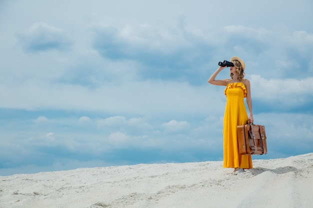 Woman with suitcase looking in binoculars Premium Photo