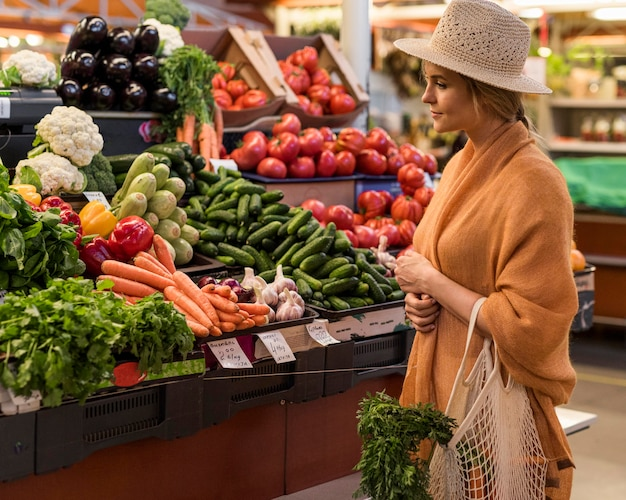 Woman with summer hat buying healthy food Free Photo