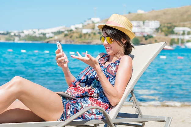 Donna con occhiali da sole e cappello alla ricerca di un cellulare Foto Gratuite