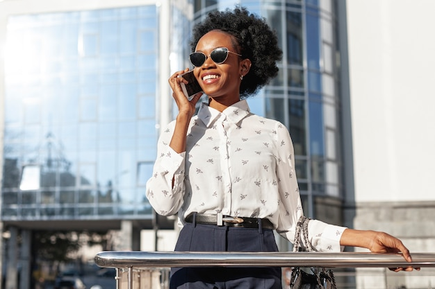 Woman with sunglasses talking over phone Free Photo