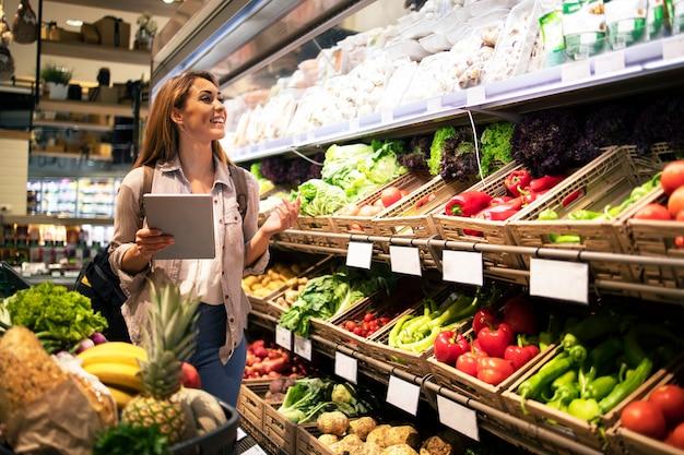 Donna con tablet acquisto di cibo sano nel supermercato drogheria Foto Gratuite