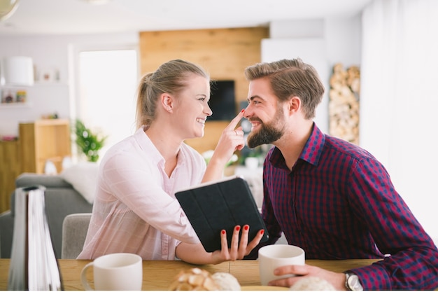 Woman with tablet touching boyfriend's nose Free Photo
