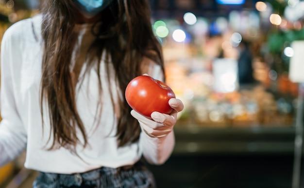 サージカルマスクと手袋をした女性が、コロナウイルスのパンデミックの後にスーパーマーケットで買い物をしています。サージカルマスクを持つ少女はトマトを買うつもりです。 無料写真