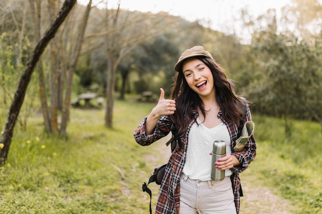 Woman with thermos gesturing thumb-up Premium Photo