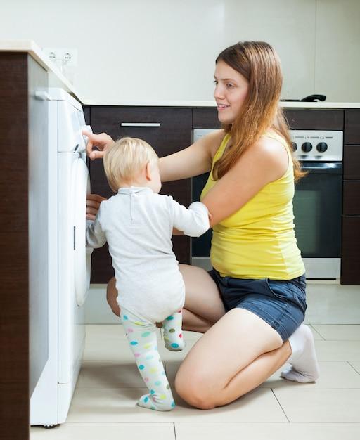 Woman with toddler using washing machine Free Photo