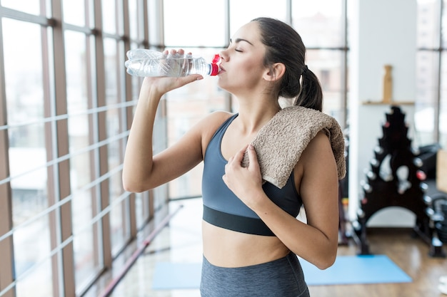 Woman with towel drinking in gym Free Photo