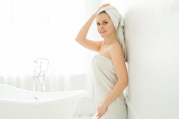 Woman with towel on head and body after shower Free Photo
