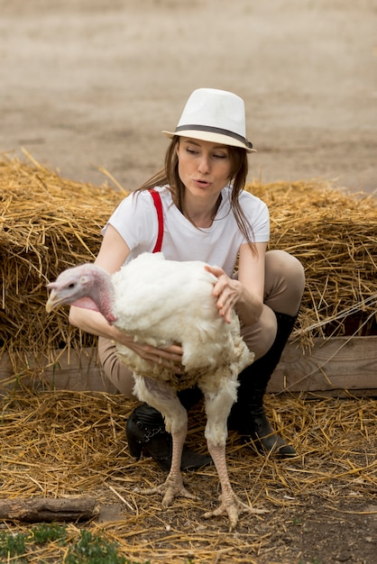 Woman with a turkey on a farm Free Photo