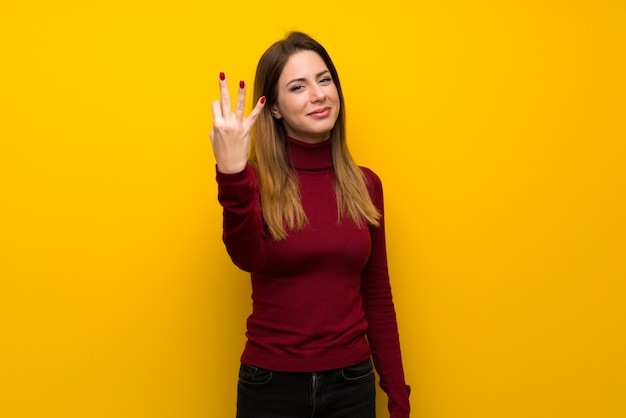 Woman with turtleneck over yellow wall happy and counting three with fingers Premium Photo