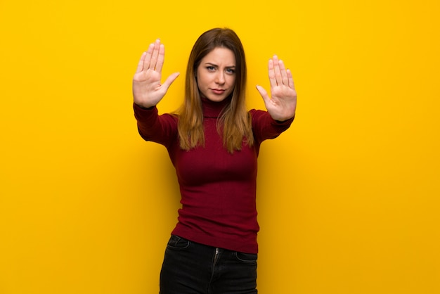 Woman with turtleneck over yellow wall making stop gesture and disappointed Premium Photo