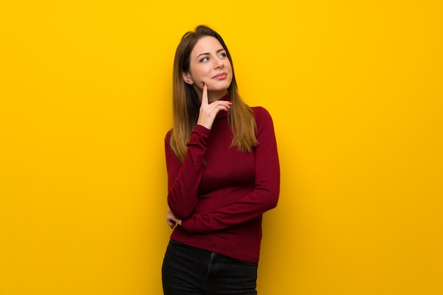 Woman with turtleneck over yellow wall thinking an idea while looking up Premium Photo