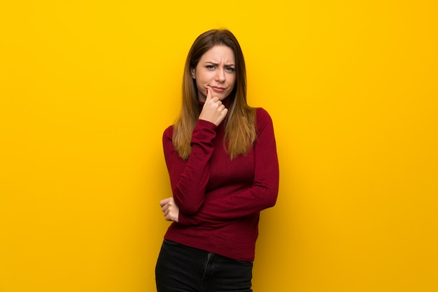 Woman with turtleneck over yellow wall thinking Premium Photo