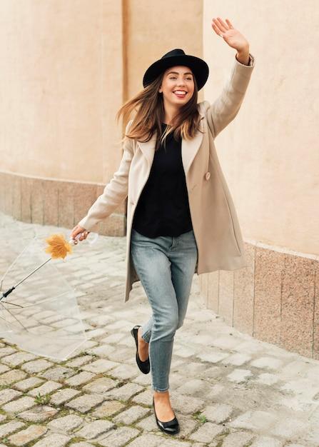 Donna con l'ombrello con il braccio alzato Foto Gratuite