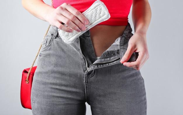 ボタンを外したジーンズの女性は、パッドを手に持っています。 Premium写真
