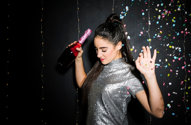 Woman with upping hands holding bottle of champagne near tossing confetti Free Photo