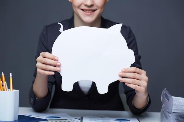 Woman with a white piggy bank Free Photo