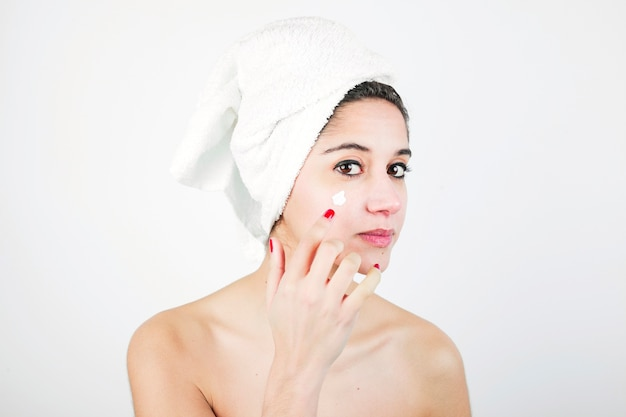 Woman with white towel wrapped around her head applying cream over the face Free Photo