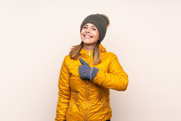 Woman with winter hat over wall giving a thumbs up gesture Premium Photo