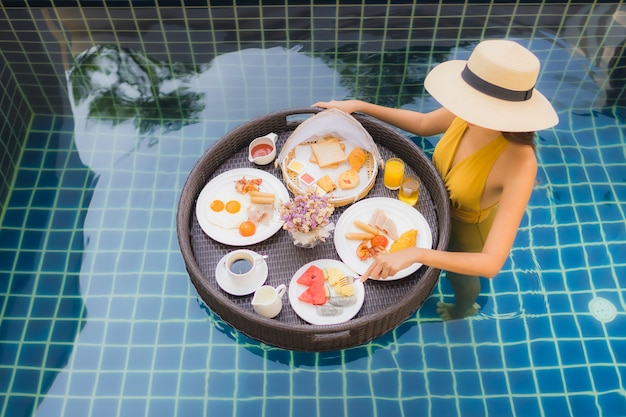 Woman with with breakfast floating around swimming pool Free Photo