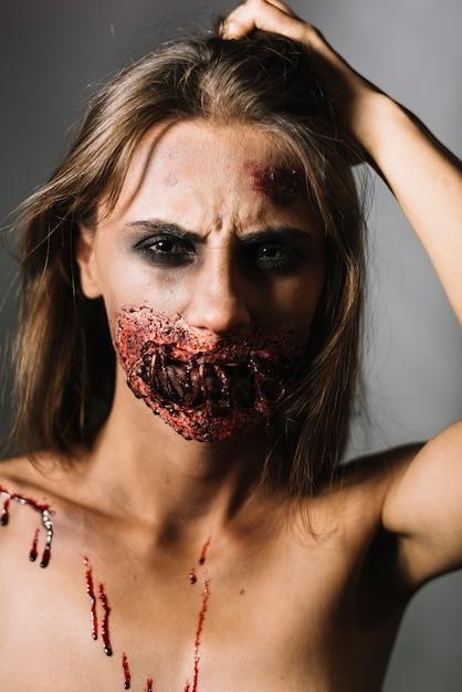 Donna con la faccia ferita che graffia la testa Foto Gratuite