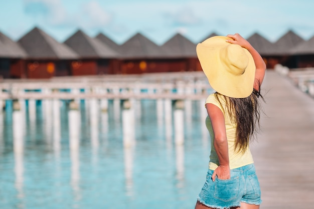 Woman with yellow hat relaxing at swimming pool in exotic resort Premium Photo