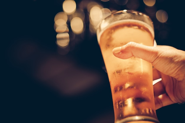 Woman with yellow nail polished holding glass of cold beer with beautiful bokeh, dark tone Premium Photo