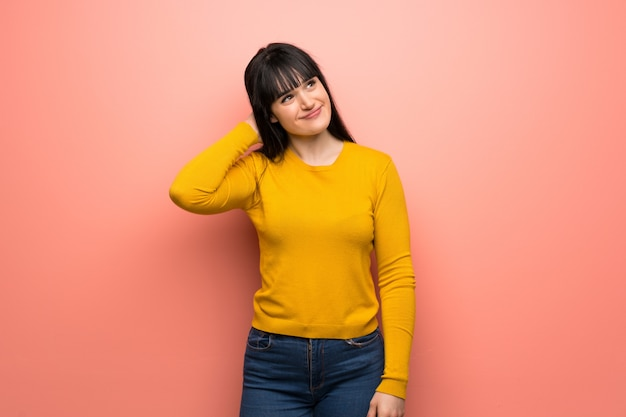 Woman with yellow sweater over pink wall thinking an idea while scratching head Premium Photo
