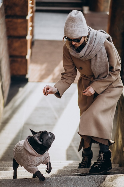 Woman withg her pet french bulldog walking out Free Photo