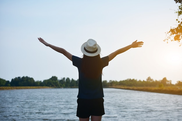 The woman wore a white t-shirt and a hat, standing on the river and the two hands on the sky. Premium Photo
