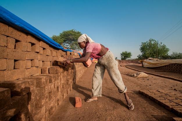 女性労働者はレンガ工場で次のプロセスのためにレンガを配置します Premium写真
