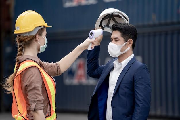 얼굴 의료 마스크와 안전 드레스에서 여자 노동자 작업자 사람들에 측정 온도. 프리미엄 사진