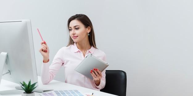 Женщина работая на столе пока держащ таблетку Premium Фотографии