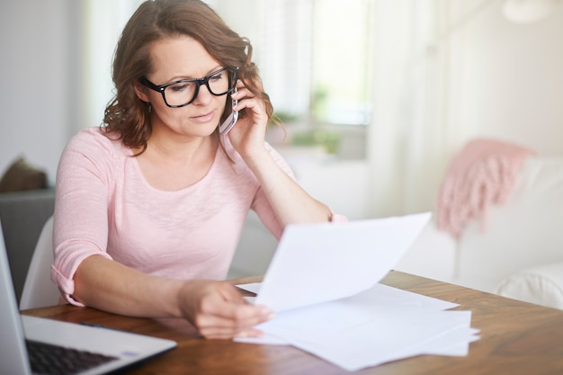 Женщина работает дома и звонит по телефону Бесплатные Фотографии