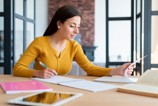 Woman working  and checking her notes Free Photo