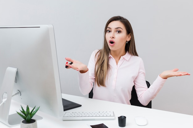 Woman working at desk not knowing what she did Premium Photo